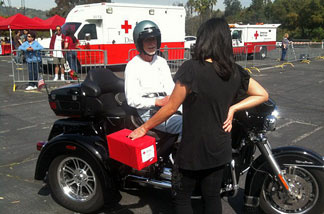 Motorcyclist donor Buzz Smith speaks with Red Cross volunteer at a drive-through donation stop for the Red Cross' Japan Earthquake Tsunami Fund on March 14, 2011.