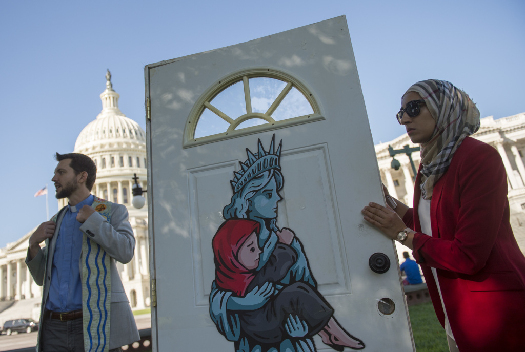 Religious leaders and activists from the Church World Service hold up a door during a protest Wednesday urging Congress to pressure President Trump to allow more refugees to enter the U.S.