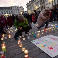 Persons light candles during a candle light vigil to the victims of the Paris attacks in Brussels' Molenbeek district, on November 18, 2015.