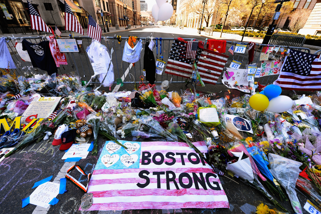 Items are placed by people visiting a makeshift memorial for victims near the site of the Boston Marathon bombings at the intersection of Boylston Street and Berkley Street.