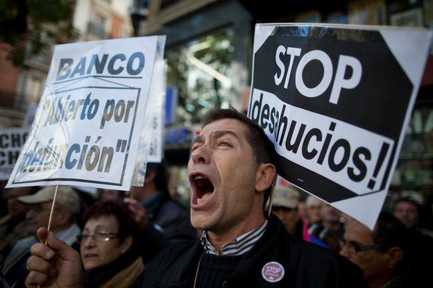 A demonstrator shouts during a protest against housing evictions in Madrid last month. The sign to his right reads,