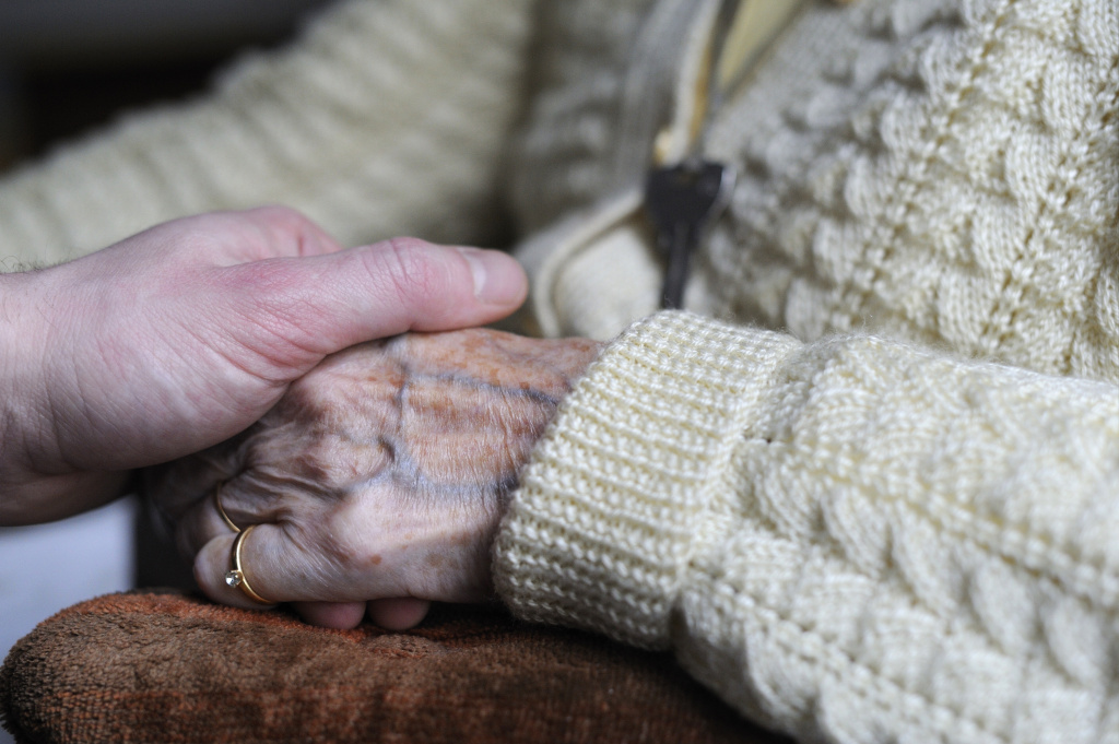 A woman, suffering from Alzheimer's desease, holds the hand of a relative on March 18, 2011 in a retirement house in Angervilliers, eastern France.