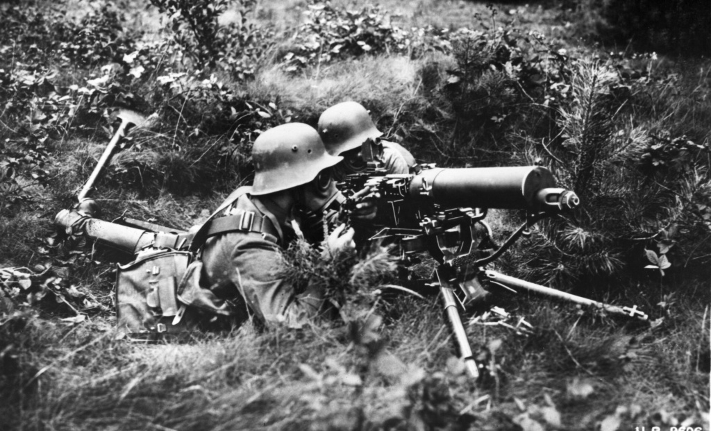 German machine gunners wearing gas masks during a WWI gas attack.