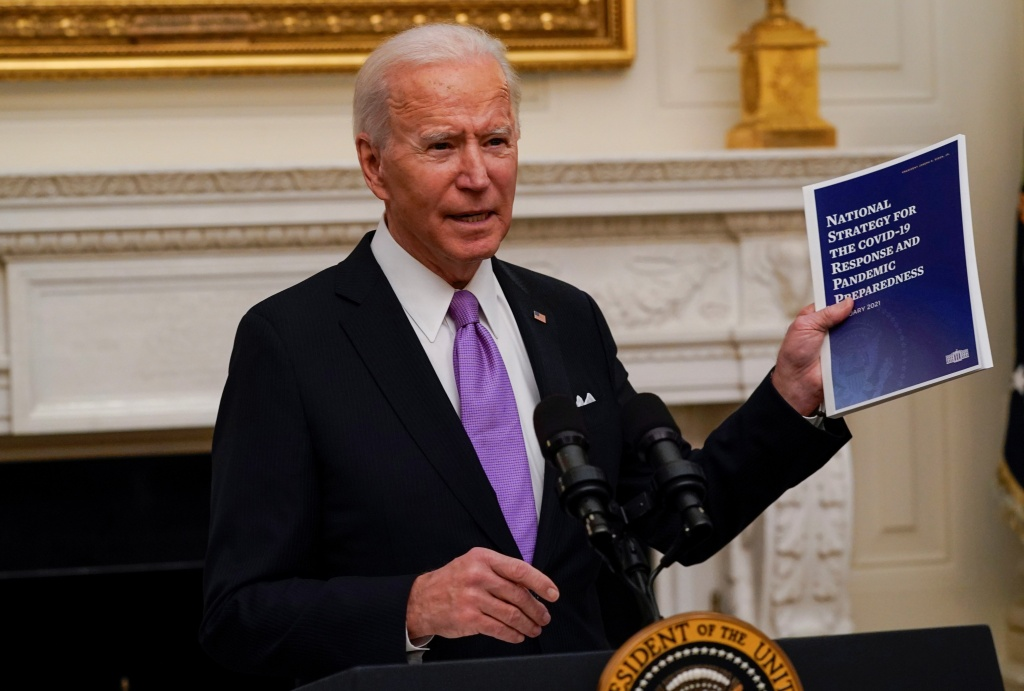 President Joe Biden holds a booklet as he speaks about the coronavirus in the State Dinning Room of the White House, Thursday.
