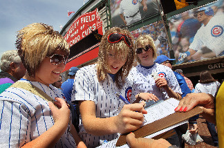 Chicago Cubs fan Jessica Polte signs a petition urging the team to move their spring training camp out of Arizona prior to the Cubs game against the Pittsburgh Pirates at Wrigley Field May 14, 2010 in Chicago, Illinois.