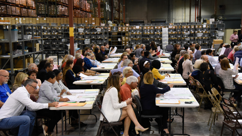 Volunteer observers keep watch Friday as election workers at tables examine ballots during a hand recount of votes cast in Palm Beach County for the U.S. Senate race.