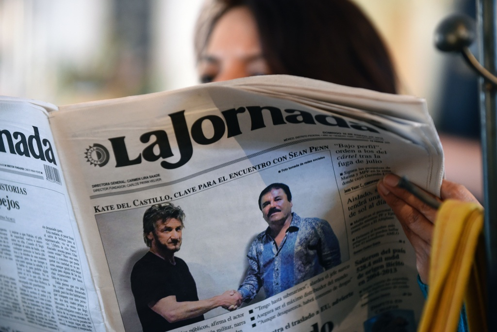 A woman reads La Jornada newspaper in Mexico City which shows a picture of drug lord Joaquin Guzman, aka