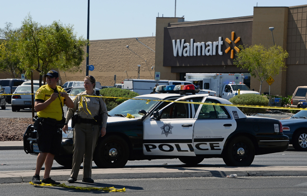 LAS VEGAS, NV - JUNE 08:  Las Vegas  Metropolitan Police Department officers put police tape up outside a Wal-Mart on June 8, 2014 in Las Vegas, Nevada. Two officers were reported shot and killed by two assailants at a pizza restaurant near the Wal-Mart. The two suspects then reportedly went into the Wal-Mart where they killed a third person before killing themselves.  (Photo by Ethan Miller/Getty Images)
