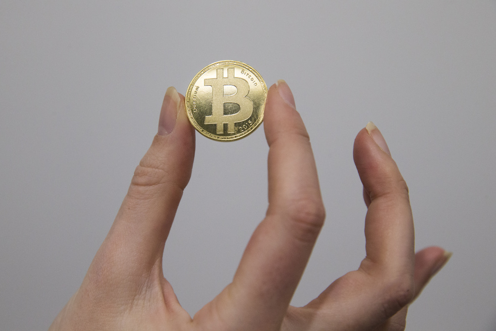 A person holds a visual representations of the cryptocurrency Bitcoin, at La Maison du Bitcoin in Paris on January 17, 2018.