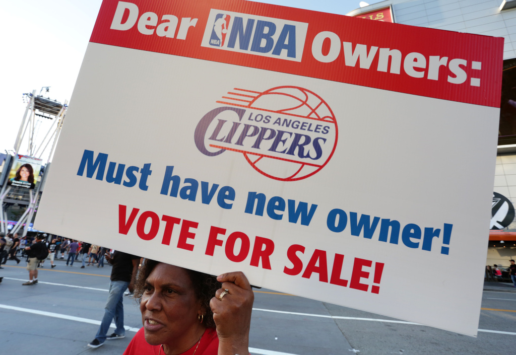 Susan Wright holds a sign protesting racist comments made by L.A. Clippers owner Donald Sterling outside Staples Center before a playoff game on April 29, 2014 in Los Angeles, California. Clippers owner Donald Sterling was banned for life today by the NBA and barred from having any association with the team and ordered to pay a $2.5 million fine.
