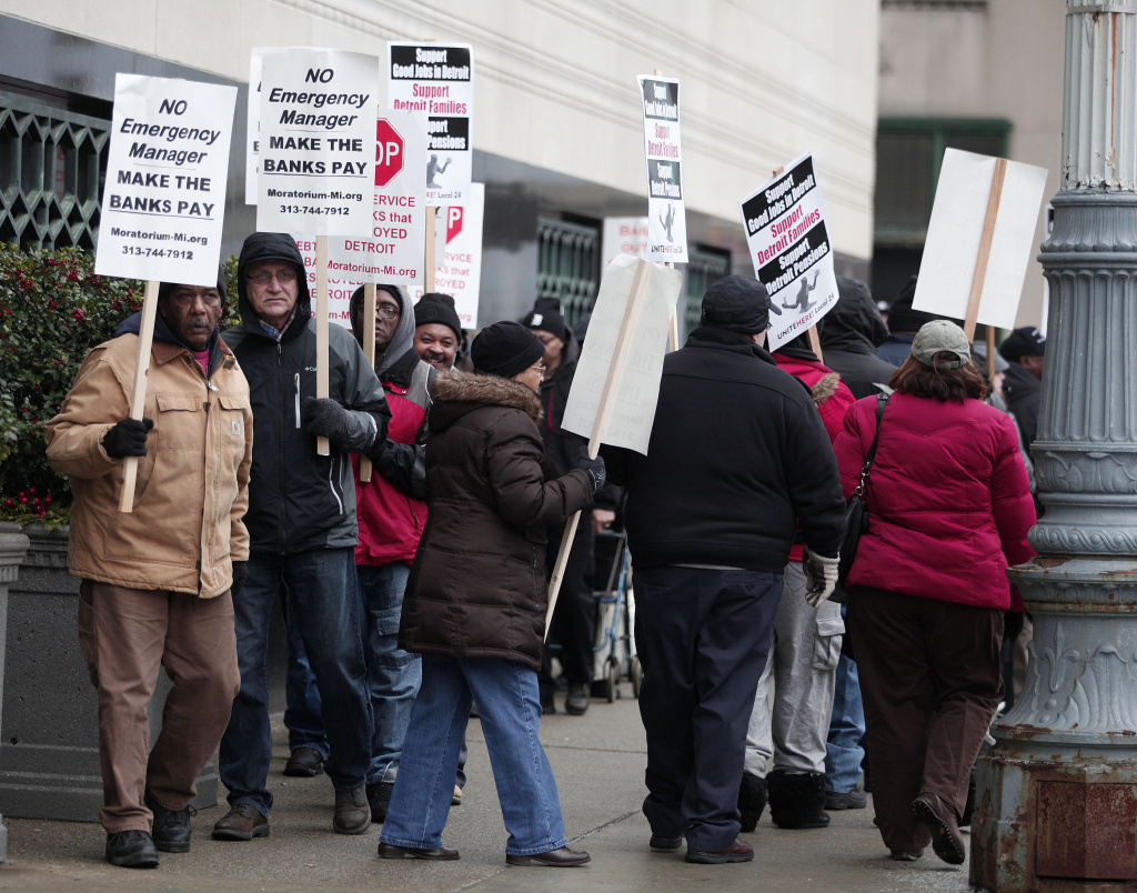 People protest outside the U.S. Courthouse where federal bankruptcy Judge Steven Rhodes is to rule on Detroit's Chapter 9 bankruptcy eligibility Dec. 3, 2013 in Detroit, Michigan. Detroit is the largest city in U.S. history to file for bankruptcy.