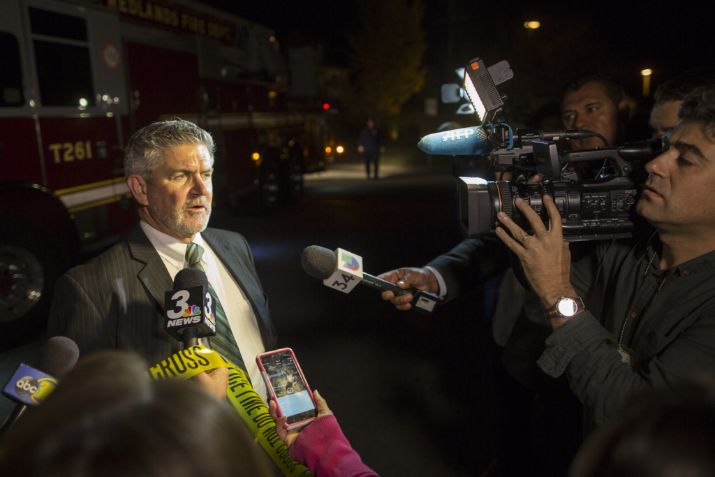 Carl Baker of the City of Redlands speaks to media near Center Street and Pine Avenue on Wednesday night, Dec. 2, 2015 as authorities serve a search warrant following a mass shooting inside the the Inland Regional Center in San Bernardino on Wednesday, Dec. 2, 2015.