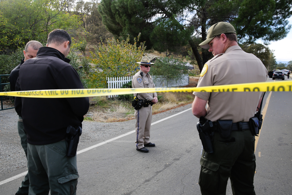 Law enforcement officers stand near one of many crime scenes after a shooting on November 14, 2017, in Rancho Tehama, California. Four people were killed and nearly a dozen were wounded when a gunman went on a rampage at multiple locations.