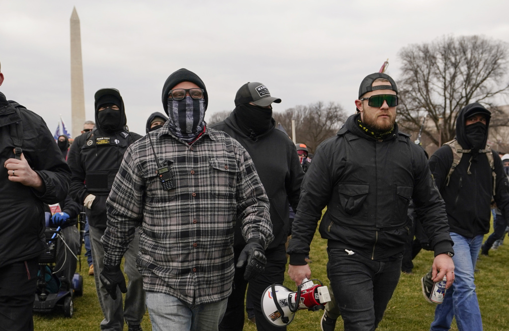 Proud Boy members Joseph Biggs (left) and Ethan Nordean, carrying a megaphone, walk toward the U.S. Capitol on Jan. 6. They were among four people indicted over conspiring to attack the Capitol.