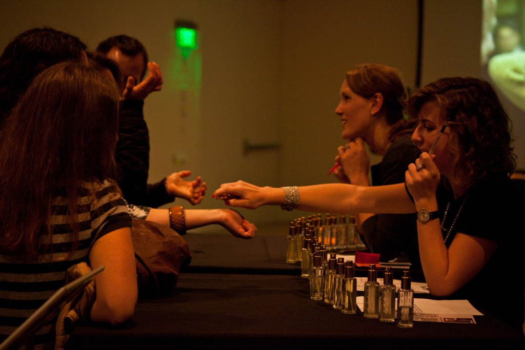 Visitors try on scents at the
