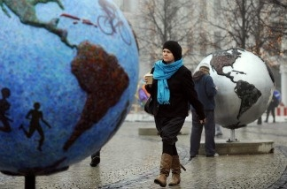 A woman walks between displays, entitled 'Cool Globes,' an exhibition about combating global warming and climate change.