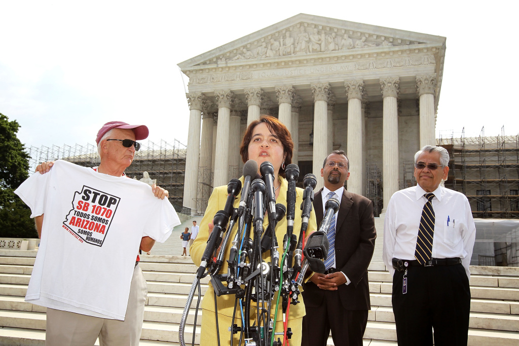 Marielena Hincapié, executive director of the National Immigration Law Center, speaks as Deepak Bhargava (2nd R), Executive Director of the Center for Community Change, and Eliseo Medina (R), International Secretary-Treasurer of Service Employees International Union, listen in front of the U.S. Supreme Court June 25, 2012 in Washington, DC. The Supreme Court has struck down three parts of the Arizona anti-illegal immigration law, but upheld the controversial