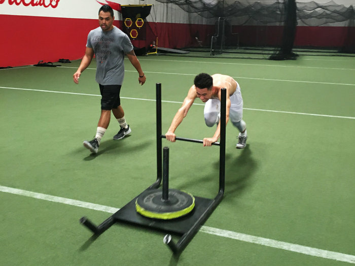 Badminton player Howard Shu pushes a weight sled designed to help improve his speed and explosive power on the court. Shu, 25, of Anaheim, Calif., will be the sole U.S. men's singles player in badminton at the Olympics.