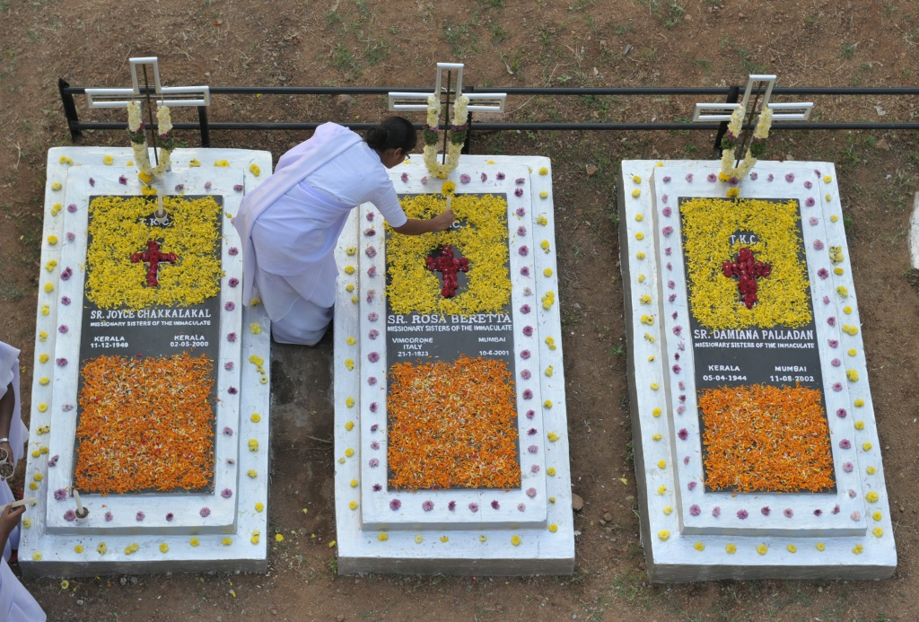 Indian Catholic nuns decorates the graves of deceased sisters at a cemetery during All Souls Day in Hyderabad on November 2, 2016.