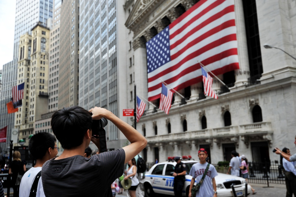 Tourists pose for photographs in front of the New York Stock Exchange.