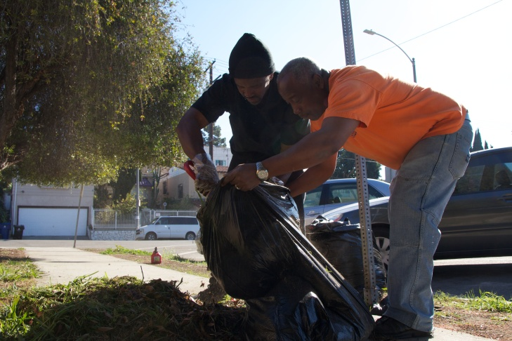 Karl Scott (R) helps General Dogon (L) shovel leaves into a trash bag. Dogon said that among other debris, he found broken beer bottles and empty marijuana vials.