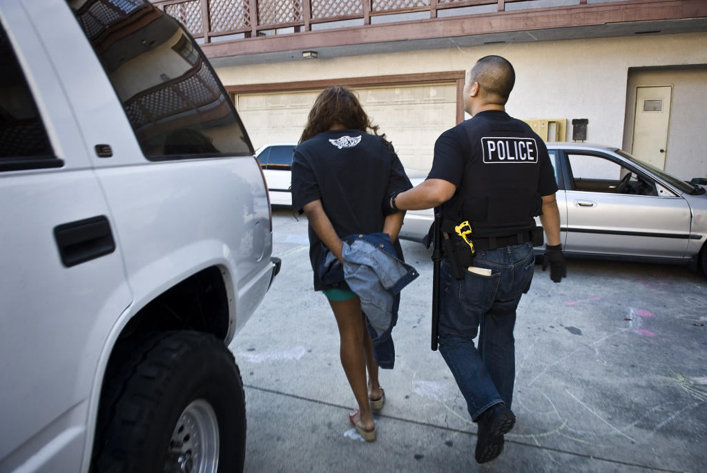 After arresting Toya Latrice Daniels, 38, Buena Park police officer James Woo, right, walks Daniels out her apartment complex and to his patrol car.