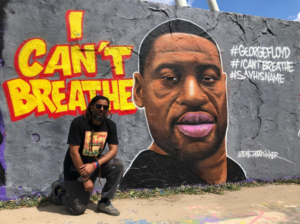 Graffiti artist Eme Freethinker kneels in front of his portrait of George Floyd, which he painted on one of the last remaining sections of the Berlin Wall.