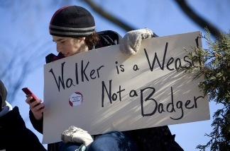 Juliet Lena of Kansasville, Wis., uses her phone to keep track of news as she joins protesters to kill Wisconsin Gov. Scott Walker's bill during a rally at the Capital Building on Feb. 18, 2011 in Madison, Wis.