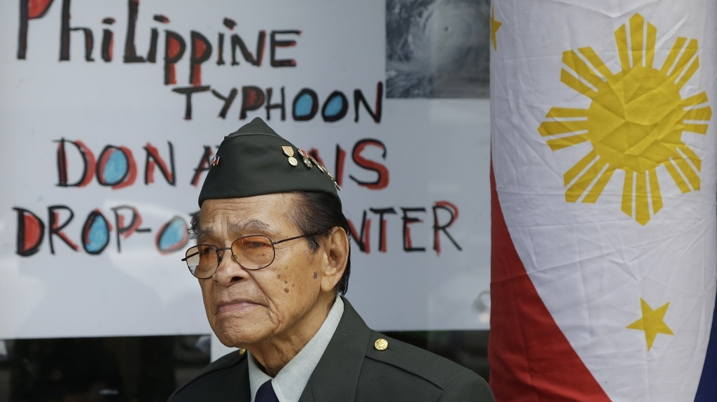 Former U.S. Army soldier Alfredo Carino stands at the door of the West Bay Pilipino Multi-Service Center in San Francisco while volunteering with other veterans to accept donations for victims of Typhoon Haiyan.