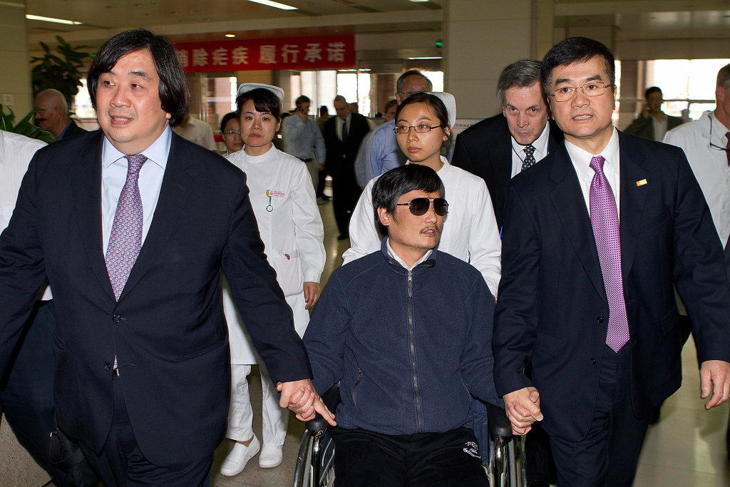 Chinese dissident Chen Guangcheng (C) holds hands with U.S. Ambassador to China Gary Locke (R) May 2, 2012 in Beijing, China.