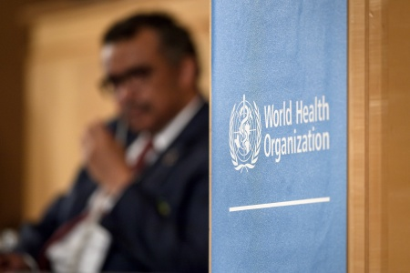 World Health Organization Director-General is seen behind a sign of the WHO during the opening day of the World Health Assembly on May 21, 2018 in Geneva.