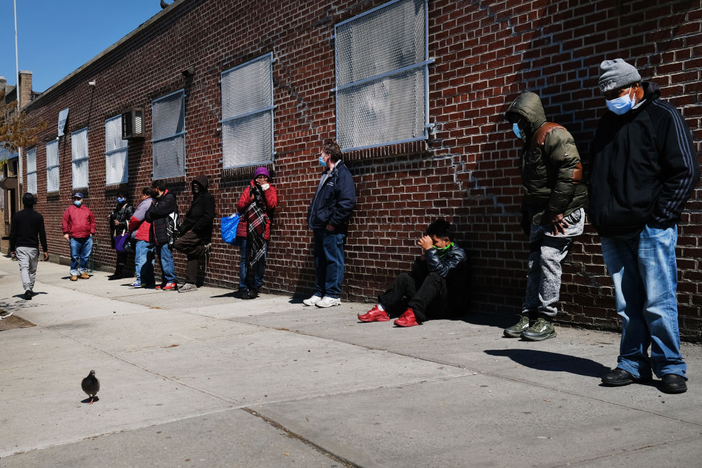 People wait in line to receive food at a food bank on April 28, 2020 in the Brooklyn borough of New York City.
