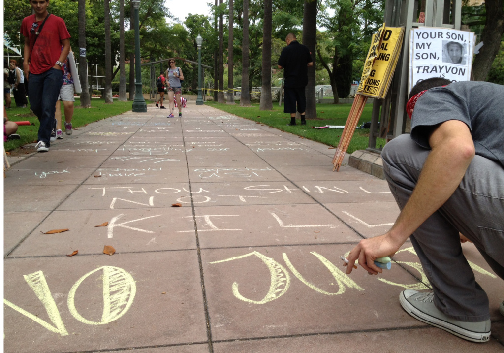Protesters chalked slogans in front of Anaheim's City Hall on Sunday, July 21, 2013, a year after a police shooting sparked violence in the community.