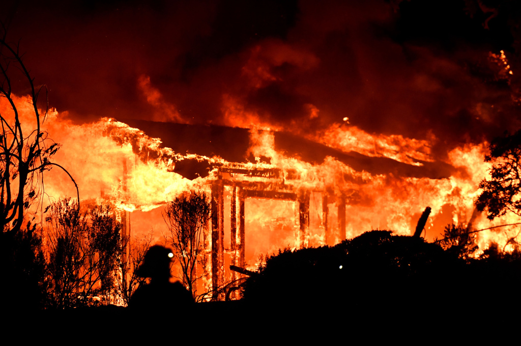 Firefighters assess the scene as a house burns in the Napa wine region of California on October 9, 2017, as multiple wind-driven fires continue to ravage the area burning structures and causing widespread evacuations.