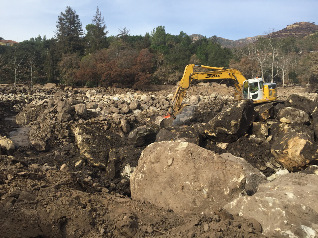Crews at Cold Springs Basin in Montecito use excavator machines to move giant boulders brought there by the winter's first heavy storm.
