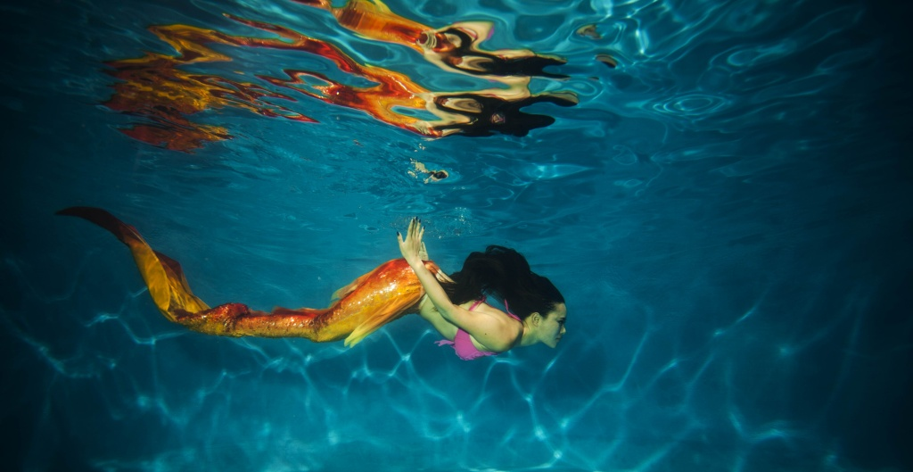 This photo taken on July 26, 2015 shows a woman clad in her self-made mermaid costume swimming in a pool in China's southwest Chongqing municipality.