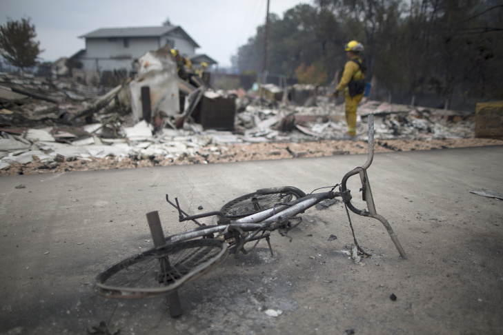 The remains of a bicycle are seen among the ruins of structures burned by the Valley Fire on September 14, 2015 in Middletown, California.