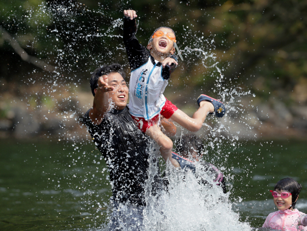 Family members play in the river at Shimanto city in Kochi prefecture on August 14, 2013.