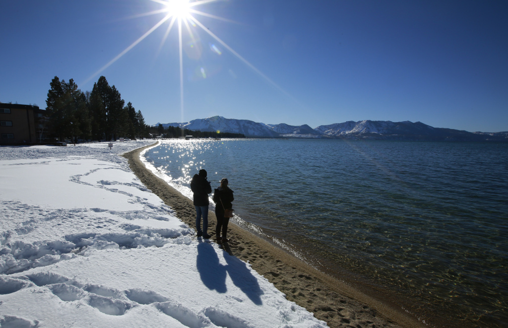 Sunlight shimmers off the snow and waters of Lake Tahoe, Monday, March 5, 2018, in South Lake Tahoe, Calif.