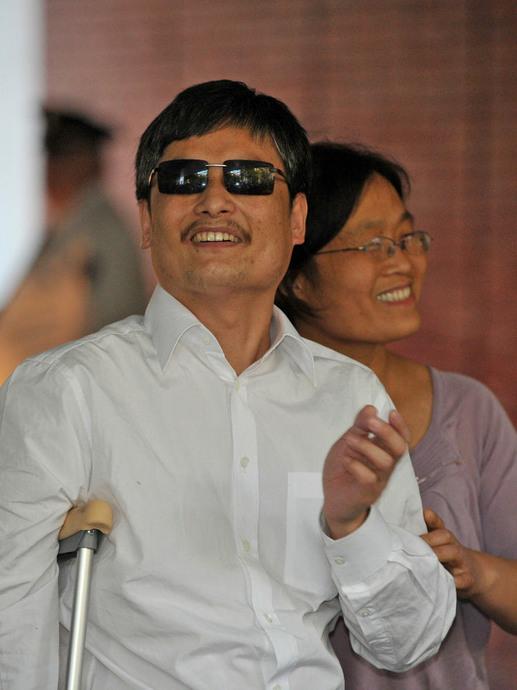 Chinese activist Chen Guangcheng and his wife Yuan Weijing arrive at an apartment complex in New York on Saturday.