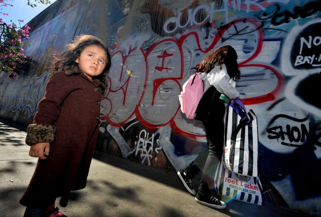 Three year old Saria Amaya waits with her mother after receiving shoes and school supplies during a charity event at the Fred Jordan Mission in Los Angeles.