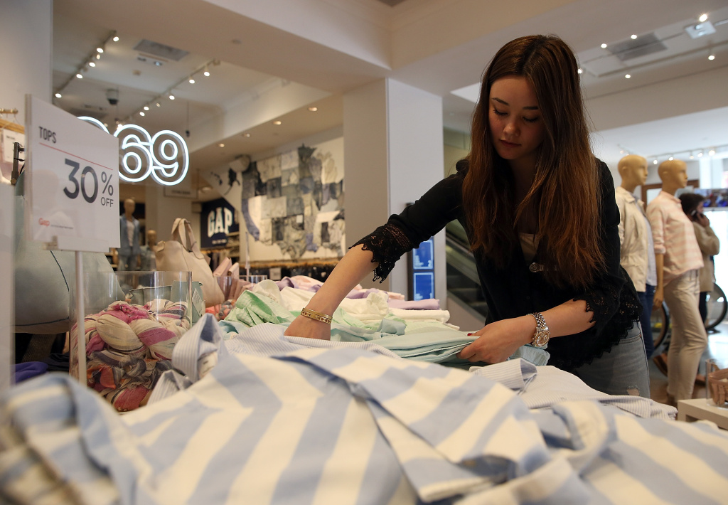 Gap employee Shinju Nozawa-Auclair folds clothes at a Gap store on February 20, 2014 in San Francisco, California.