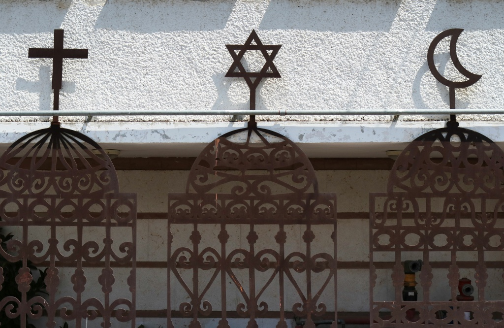 A Picture taken on April 27, 2016 shows the symbols of the three monotheistic religions, Christianity, Judaism and Islam, on the front of an Arab Jewish centre in the northern port city of Haifa.