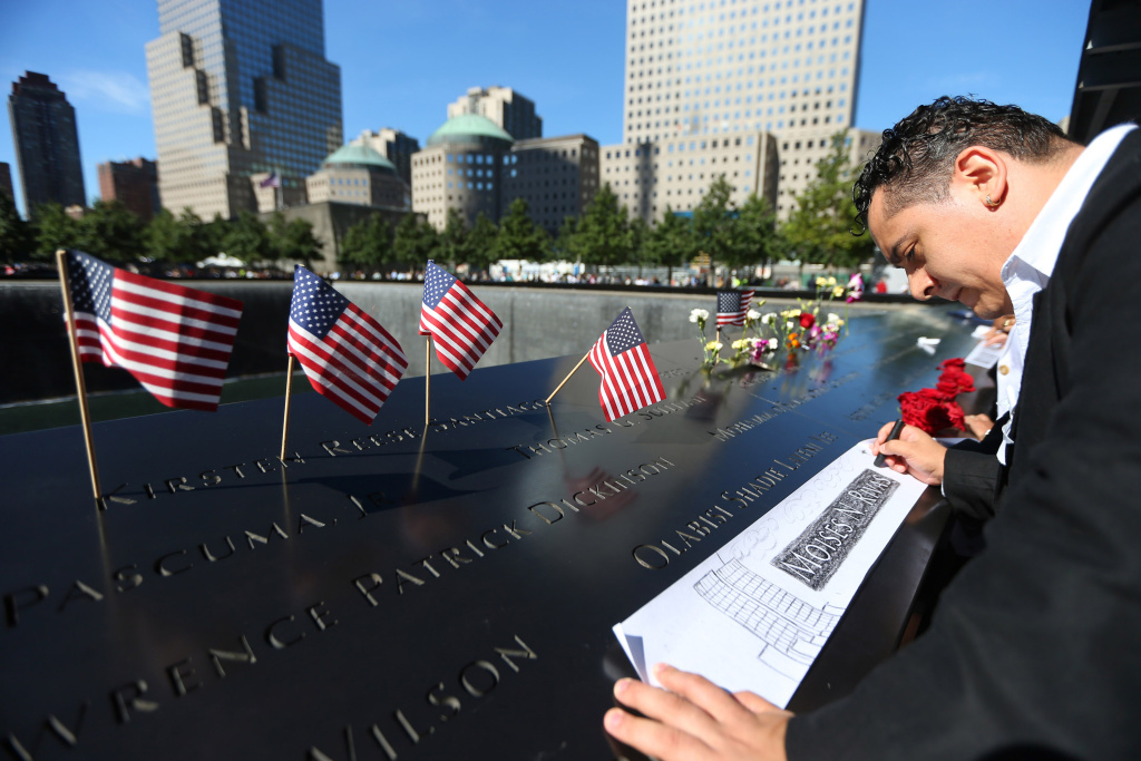 Clever Rivas makes a rubbing of his brother Moises N. Rivas' name during memorial ceremonies for the 11th anniversary of the terrorist attacks on lower Manhattan at the World Trade Center site, September 11, 2012.