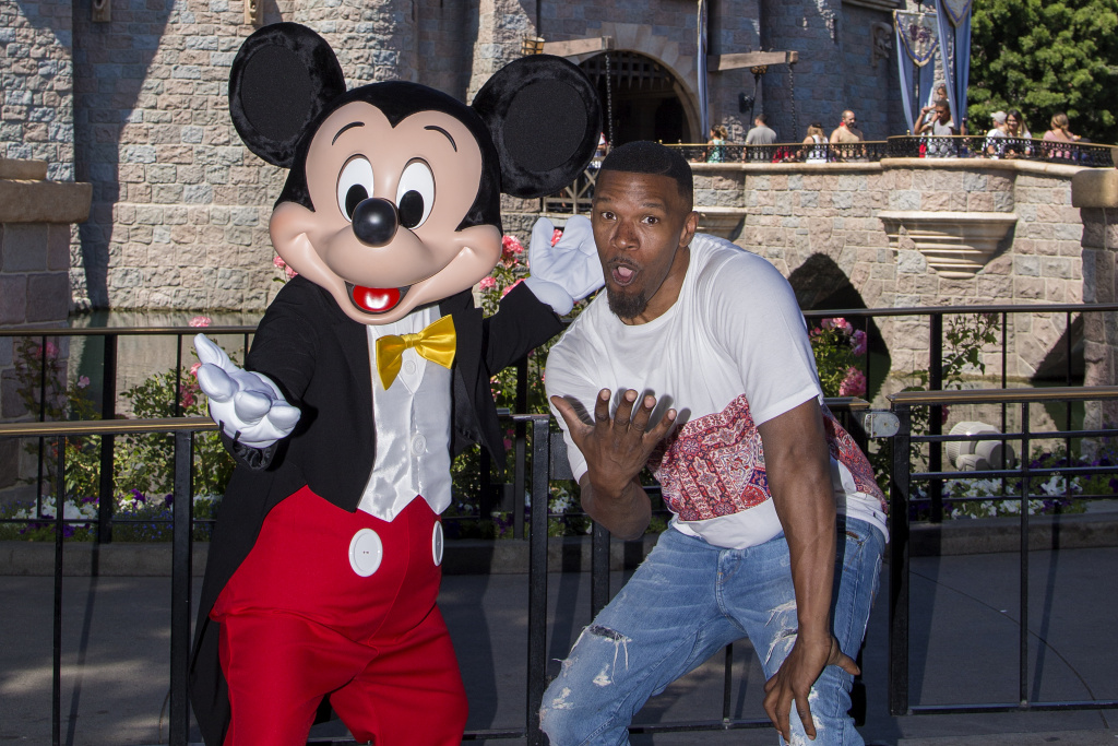 Actor Jamie Foxx meets Mickey Mouse in front of the Sleeping Beauty Castle at Disneyland in Anaheim, California on July 3, 2017.