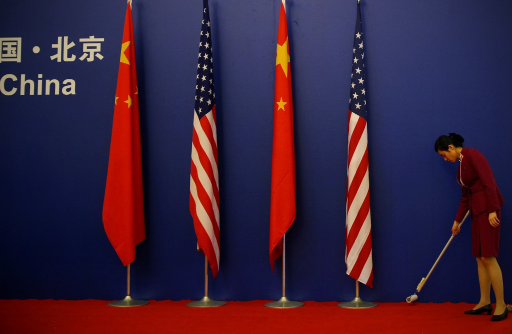 A waitress cleans the carpet in front of American and Chinese flags ahead of a press conference for the China-U.S. Strategic and Economic Dialogue (S&ED) at the Great Hall of People on May 25, 2010 in Beijing, China.