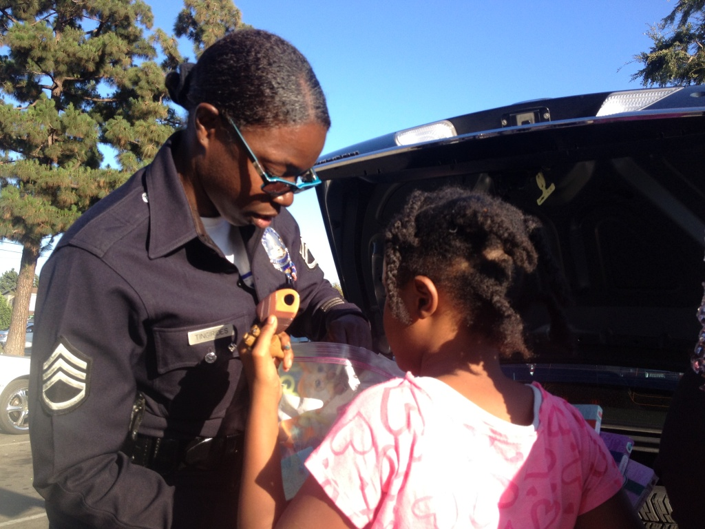 LAPD Sgt. Emada Tingirides hands out beaded bracelets and books to a girl in the Nickerson Gardens Housing Project in Watts.