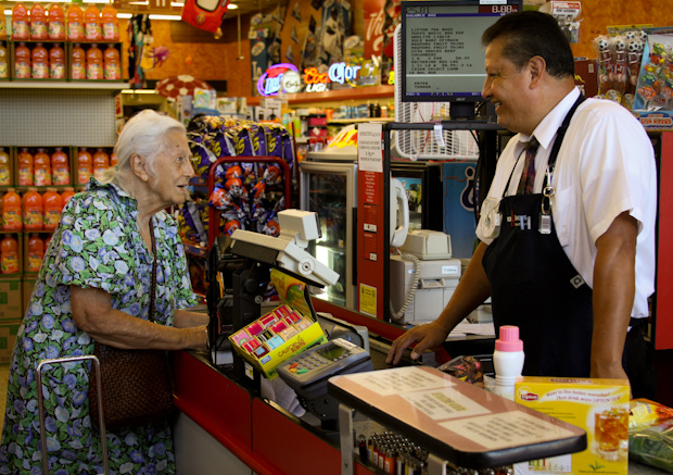 Super A night manager, Hector Reyes, chats with a customer at the check out.
