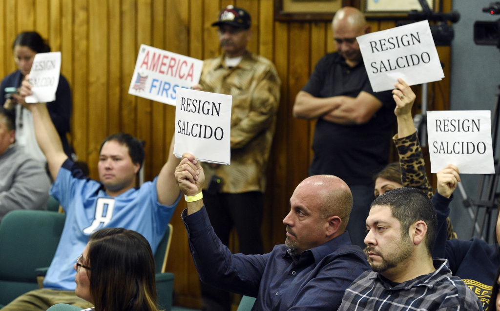 Pico Rivera, Calif. City Council meeting attendees hold up signs during a city council meeting at Pico Rivera City Hall on Tuesday, Feb. 13, 2018, in Pico Rivera, Calif. The city council passed a resolution Tuesday asking for the resignation of city councilman and El Rancho High School teacher Gregory Salcido, who was recorded making anti-military remarks to his students in January.