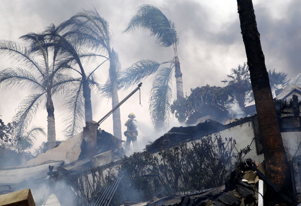 A firefighter stands under windswept palm trees as he hoses down smoldering debris in Ventura, Calif., Tuesday, Dec. 5, 2017. Ferocious Santa Ana winds raking Southern California whipped explosive wildfires Tuesday, prompting evacuation orders for thousands of homes.